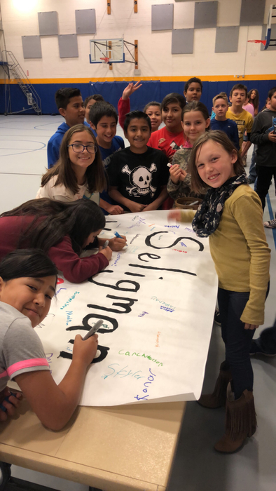 Kids signing welcome banner