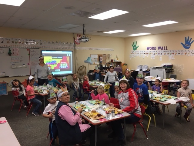 Kindergarten eating in their class room with hats they made.